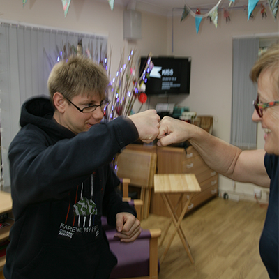 Young male fist punching support worker